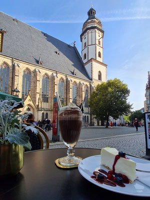 Frühstück im Café Gloria mit Blick auf die Thomaskirche: Heiße Zimtschokolade (geschmolzene Zartbitter-Schokolade mit Zucker und Zimt in heißer Milch verrührt und einer Sahnehaube), dazu Käsekuchen mit Beeren