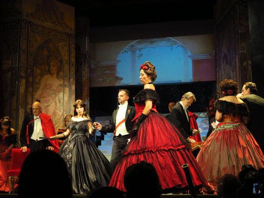Zweiter Akt, Zweites Bild: Galerie im Palast Floras. Violetta, am Arm von Baron Douphol, besucht den Ball Floras.