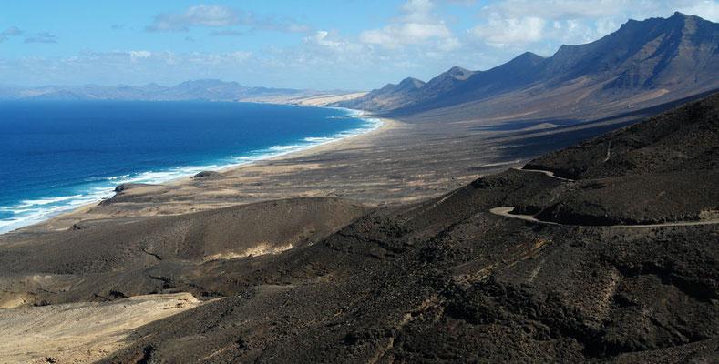 Blick vom schönsten Aussichtsplateau des Inselsüdens, Roque del Moro, nach NE zur Playa de Cofete, zur Playa de Barlovento und bis zu den Bergen von Pájara. Von den Stränden steigen die Hänge bis zum Pico de la Zarza, dem höchsten Berg der Insel (807 m)