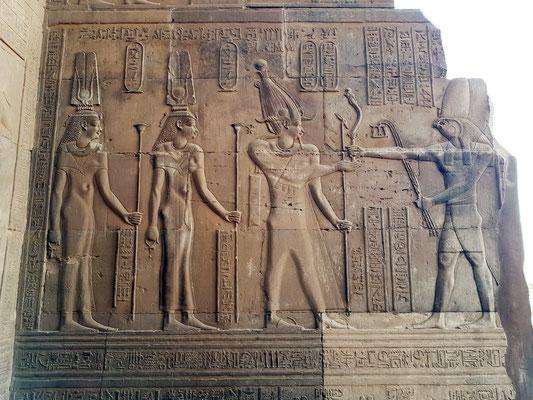 Horus schenkt Ptolemaios V. ein Schwert. In der anderen Hand hält er für den König 3 mal 100 000 Jahre Leben. Hinter Ptolemaios stehen seine Frauen Kleopatra II. und Kleopatra III.