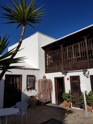 Galeriehof. Balkon mit einem Holzgitterwerk im Stil der traditionellen Inselarchitektur