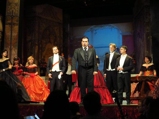 Zweiter Akt, Zweites Bild: Galerie im Palast Floras. (Alfredo lässt sich schließlich von seiner Eifersucht hinreißen und wirft das gewonnene Geld auf Violetta, quasi als Entlohnung für ihre Liebesdienste).