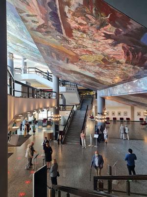 """Sighard Gille schuf 1980–1981 für die Foyers das 714 m² große und 31,80 m hohe Deckengemälde """"Gesang vom Leben"""". Es ist das größte Deckengemälde Europas."""