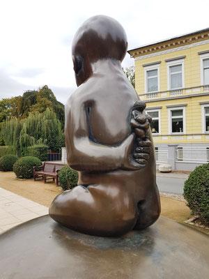 Skulptur eines Kindes, das auf einer Weltkugel mit 19 Lichtpunkten, stellvertretend für die 19 Pyrmonter Heilquellen, thront.  Auf seinem Rücken die Figurine der Venus von Willendorf