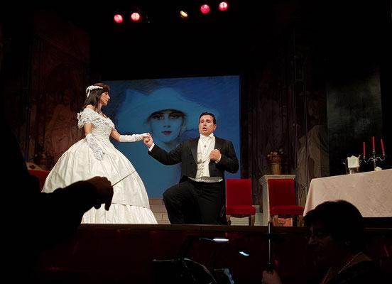Erster Akt: Salon im Haus Violettas, Alfredo erklärt Violetta seine Liebe.