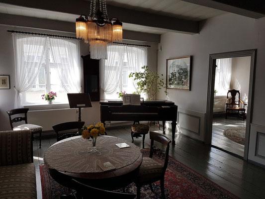 Wohnzimmer im Obergeschoss mit dem Ibach Tafelklavier. Am 24.12.1858 wurde das Klavier an den Kreisrichter Storm in Heiligenstadt geliefert (aus dem Verkaufs- und Lagerbuch der Firma Ibach).
