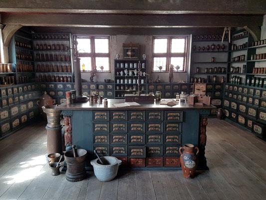 Offizin, Arbeitsraum der Apotheke, Mitte 18. Jahrhundert, Bemalung der Schubladen ist original, schädelgeschmückter Giftschrank an der Wand zwischen den Fenstern