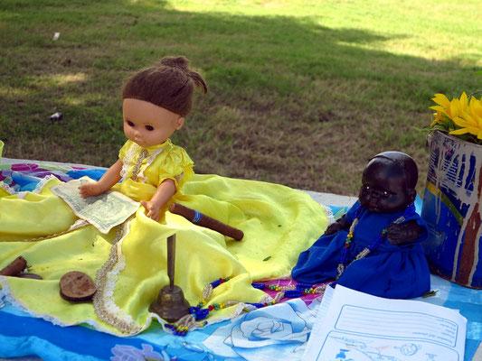 Puppen in bunten Kleidern und Opfergaben als Bestandteil des Santería-Kults