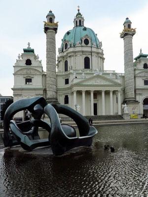 Karlsplatz mit ovalem Teich und einer Skulptur von Henry Moore, dahinter die Karlskirche