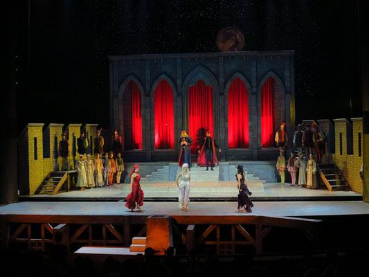Applaus (rothaarige, blondhaarige und schwarzhaaarige Fee, v.l.n.r.), Palastanlage des Königs, davor Teil der versenkbaren Kullisse (Wohnhaus)