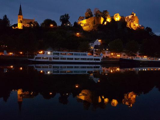 Saarburg bei Nacht, Blick von der Saar auf die Burganlage, links die evangelische Kirche