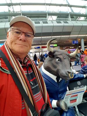 Im Flughafenterminal Düsseldorf. Das gehörnte Wesen neben mir ist kein Reisebegleiter, wenn auch stark, intelligent und ohne Widerworte.