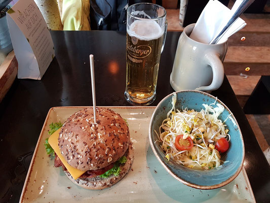 "Mittagsmenü: Veganer Burger ""Wolpertinger"" (pikanter Gemüsebratling, vegane Goldscheibe & Avocadocreme), dazu Krautknolle (Krautsalat mit Kartoffeldressing), gezapftes Radeberger Pils"