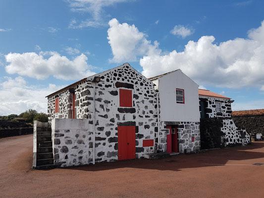 Häusergruppe mit typischen roten Fensterläden und Türen im Dorf Lajido