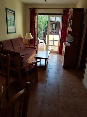 Apartment N6 (im Nordteil der Anlage), Wohnzimmer (mit Schlafcouch) und Blick zur Terrasse