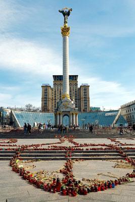 """Das 63 m hohe Unabhängigkeitsdenkmal der Ukraine, dahinter das 16stöckige Hotel """"Ukrajina"""" (bis 2001 Hotel """"Moskwa""""). Blumen und Grableuchten erinnern an die Kämpfe des Euromaidan im Februar 2014."""