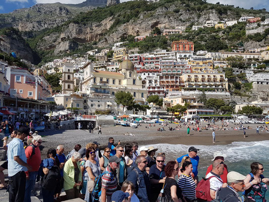Touristen an der Schiffsanlegestelle in Positano, dahinter die Chiesa di Santa Maria Assunta