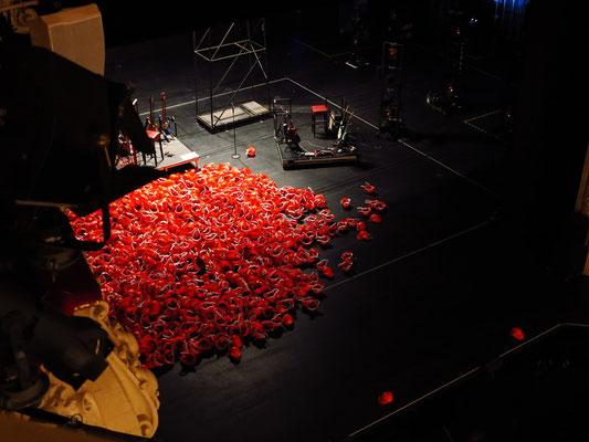 Die Schauspieler spielen in einem Berg von Bauhelmen. Bühnenbild: Mascha Mazur