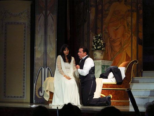 Dritter Akt, Schlafzimmer Violettas. Alfredo sinkt, um Verzeihung bittend, Violetta in die Arme.