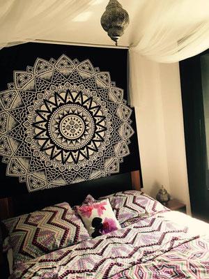 Zentral hinter dem Bett wirken Mandala Tücher als Blickfang