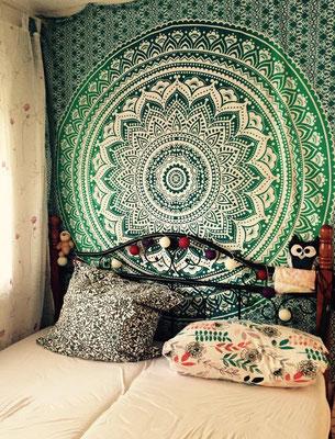 Grünes Mandala Wandtuch mit Lichterkette hinter dem Bett