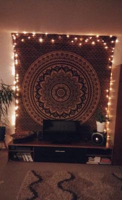 Umrahmt mit Lichterketten ist das goldene Mandala Wandtuch der Zentrale Blickfang im Wohnzimmer