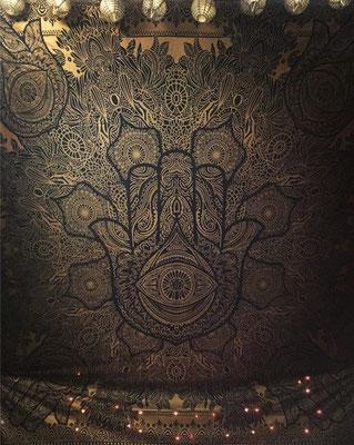 Hand der Fatima in gold auf schwarz unter einer Dachschräge