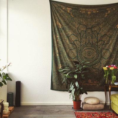 Grüner Wandbehang im Wohnzimmer mit Hand der Fatima in gold