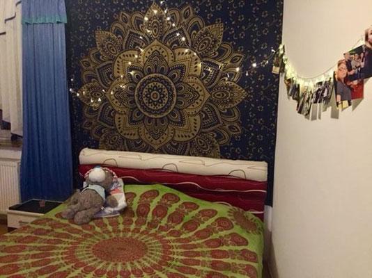 Goldene Lotusblüte auf dunkel blau an der Wand hinter dem Bett