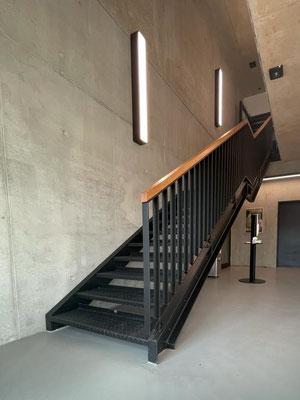 Treppe mit Flachstahlgeländer und Holzhandlauf