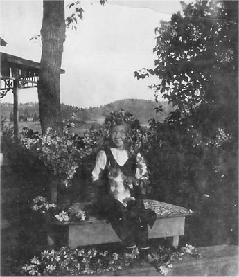 Vivian Johnson with her cat, covered in apple blossoms.