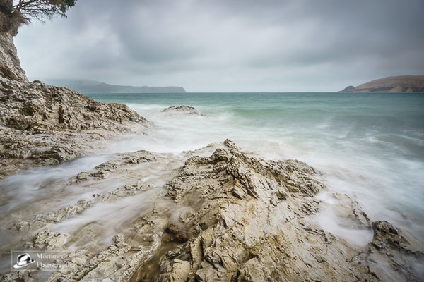 rocks in the water with dramatic cloudy ocean scenery in the background