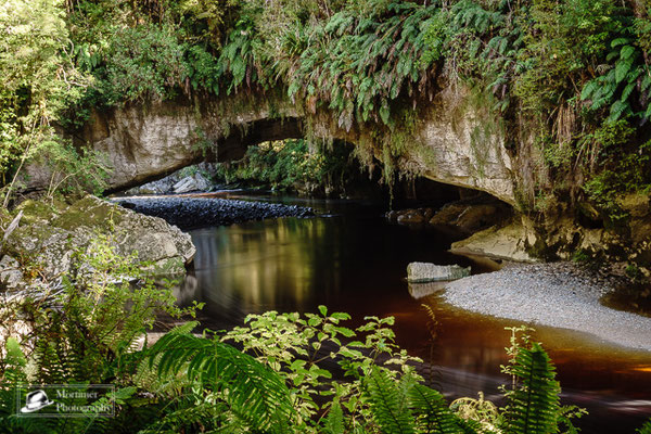 a limestone arch over a little river in the jungle