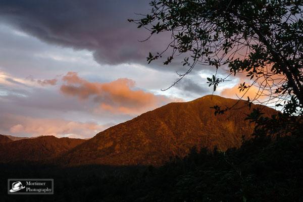 Farben des Sonnenuntergangs mit Dschungel und Bergen im Hintergrund