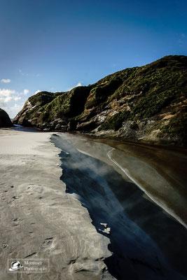 Strandkulisse mit extrem weißem Sand der vom Wind durch die Luft getragen wird