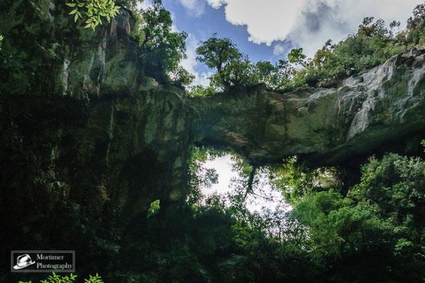 Zugewucherter Kalksteinbogen über einen Fluss mitten im Dschungel