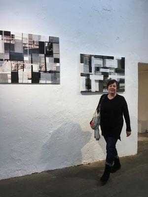 """Monika Humm vor Arbeiten aus der Serie """"global - men at work"""" im Kunstverein Ebersberg"""