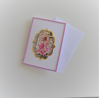 Die Karte hat ein Blumenmotiv in der Mitte und ist mit rosa Perlenstickern umrandet.