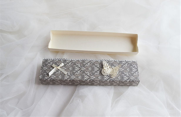 Schiebeschachtel in grau-creme. Farblich passend ist der ausgestanzte Schmetterling sowie die keine Schleife aus Stoff.