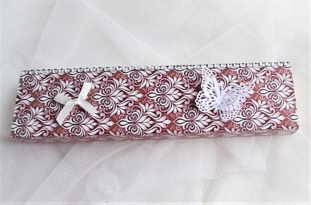 Schiebeschachtel in rot-weiß. Farblich passend ist der ausgestanzte Schmetterling sowie die keine Schleife aus Stoff.