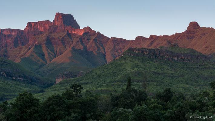 Die Berge werden von der Morgensonne rötlich angestrahlt.