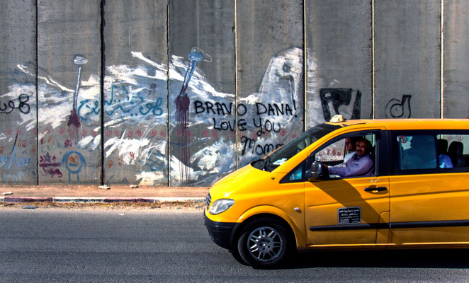 Figure 10. A serveech, or shared taxi, carrying students from nearby Al-Quds University speeds past a once impressive international protest tourist mural. Photograph taken May 2014.