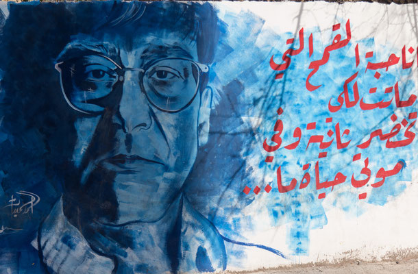 Figure 16.Ahmed Hmeedat's mural of Mahmoud Darwish. The text is adapted from Darwish's poem 'Mural'. A recent translation of the poem reads: 'I am the grain that died and became green again. There is something of life in death'. Photo taken February 2014.