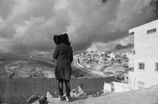 A student from Al-Quds University looks over a recent Israeli housing demolition in the foreground. The separation barrier here in Abu Dis divides that Palestinian town from Jerusalem. The Old City is visible to the left on the horizon. December 2013