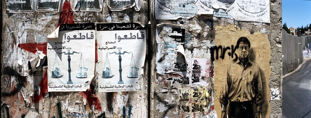 Figure 8. An image of the iconic Palestinian poet Mahmoud Darwish on the right and posters in Arabic on the left indicate local authorship of these images on the wall in Abu Dis. Photo taken 2009