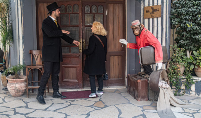 Figure 7. A doorman at the Walled Off Hotel welcomes a guest. The entrance exhibits a bit of Banksy's trademark humor. Photo taken March 2020