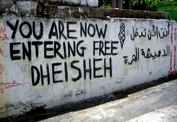 Figure 11. Inside the main entrance to Dheisheh camp. When this wall was repainted by Aysar and his collective during May 2014 and as part of the process of continuity within the camp this message was retained. Photograph taken July 2009.