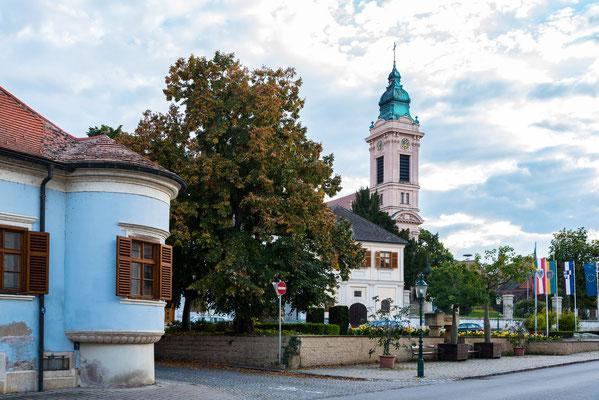 Rust am See mit evangelischer Kirche. Das Fassadenjoch und der Turm zeigen eine reiche neubarocke Stuckdekoration mit profilierten Gesimsen und Blumengebinden. Der Turm hat kannelierte Eckpilaster und trägt einen hohen Zwiebelhelm