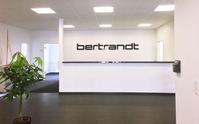 Firmenschriftzug aus Acrylbuchstaben im Eingangsbereich, montiert mit Wandabstandshaltern