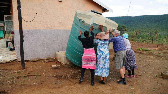 Karel und die Erzieherinnen stellen den Wassertank auf